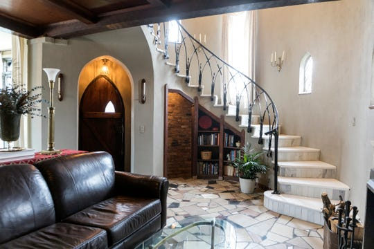 The main staircase, like the many others, is curved to the shape of its turret. The old floors are random mosaic of stone and marble. Peaked windows are set into the curve of the wall. The glimpse of brick in the center starts the stairs to the hidden room.