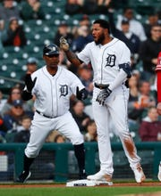 Detroit Tigers' Ronny Rodriguez, right, reacts to hitting a two-run triple as third base coach Dave Clark watches against the Los Angeles Angels in the first inning of a baseball game in Detroit, Wednesday, May 8, 2019.