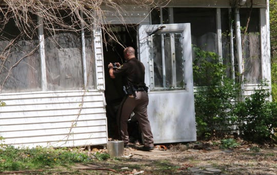 In this Monday, May 6, 2019, photo, a St. Joseph County Sheriff deputy photographs the site where a woman was fatally shot in Fawn River Township, Mich. Authorities say a 9-year-old is suspected in the shooting of a woman in her southern Michigan home.