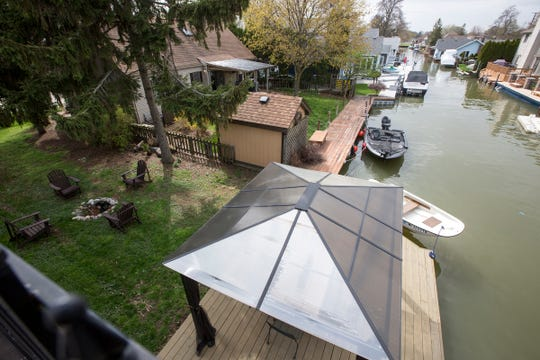 The view from the rooftop terrace goes down the canal in one direction and out to Lake St. Clair in the other. The house has 100 feet of dock and deck at the shore.