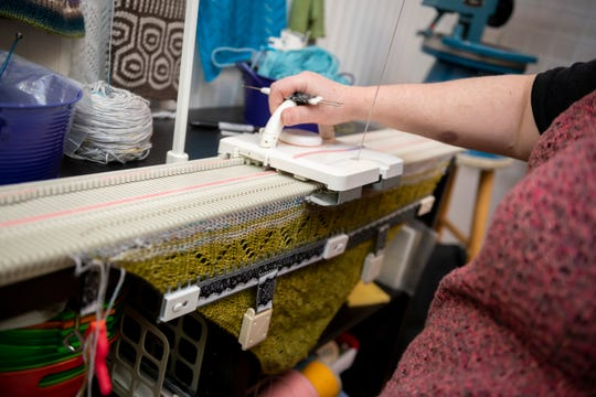 Amy Houghtalin, manager of City Knits in Harrison Twp., works on a hybrid knit litrikur patterned scarf on a knitting machine.