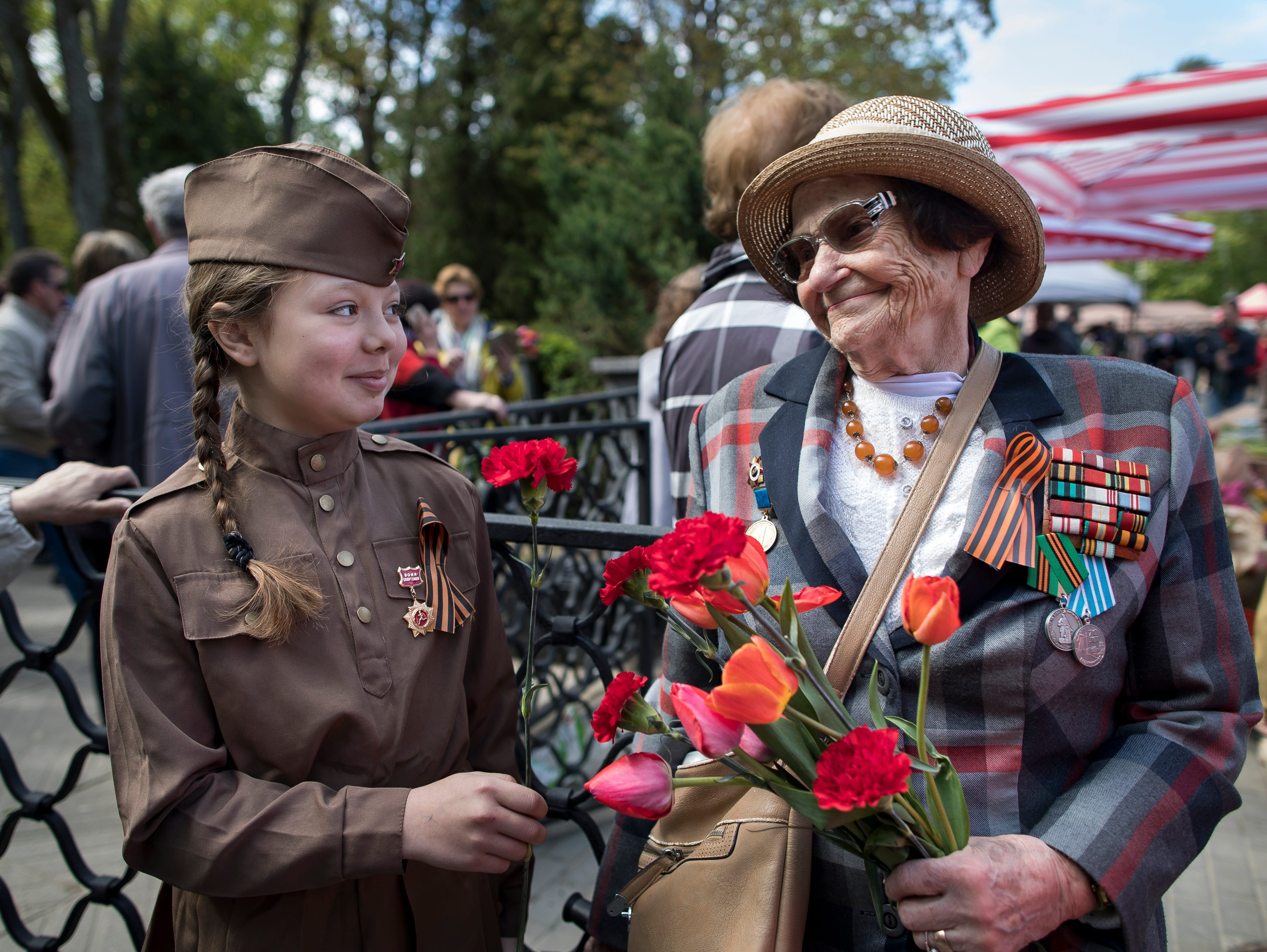 Tatijana Arhipova Efros, a 97-year-old veteran of World War II, receives flowers at the Antakalnis memorial during Victory Day celebrations in Vilnius, Lithuania, Thursday, May 9, 2019.
