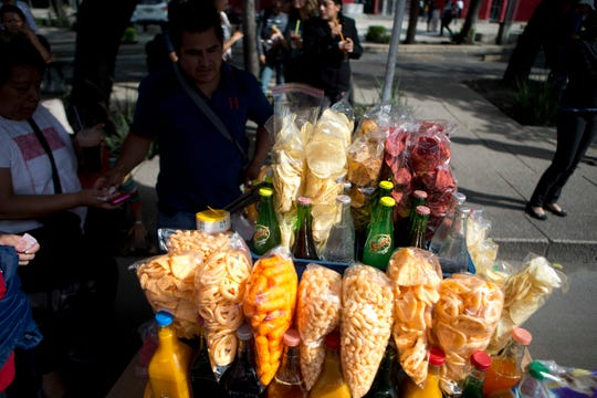 A street vendor sells fried snacks packaged in plastic bags in Mexico City.