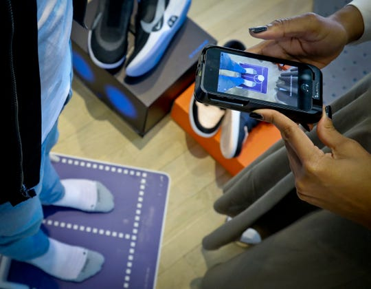 Nike officials demonstrate the company's foot-scanning tool on its app that will measure and remember the length, width and other dimensions of customers' feet after they point a smartphone camera to their toes.