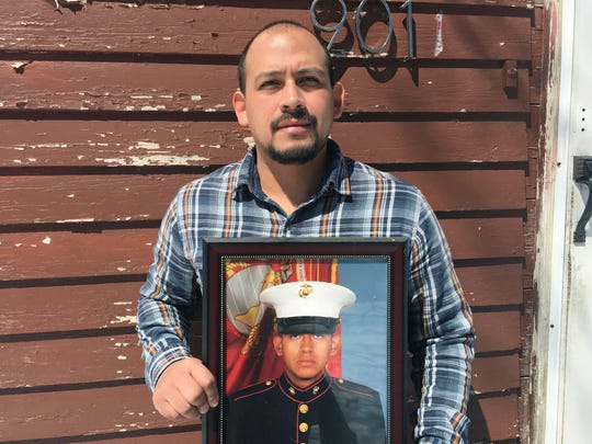 Mark Esqueda with a photo of him as a U.S.Marine, in Heron Lake, Minn. Esqueda was born in the United States but has been twice denied his request for a passport.