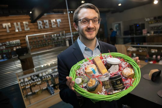 Evan Pilot, financial controller for The Reef marijuana dispensary in Detroit, holds a Mother's Day gift basket for sale.  The customizable basket, which runs between $200 and $450, can include CBD infused moisturizers, oils, body rub, and facial scrubs.