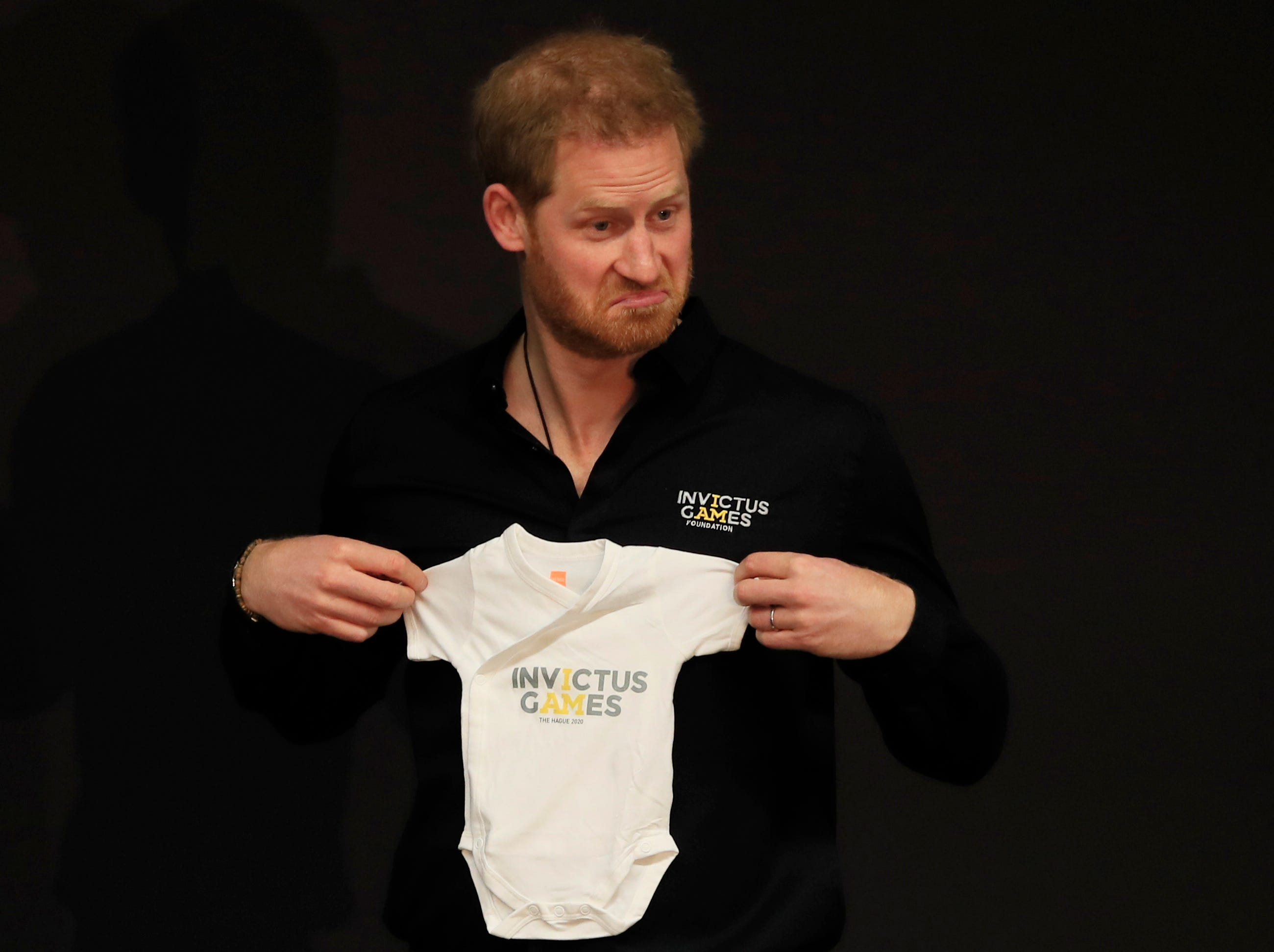 Britain's Prince Harry holds up an outfit for his newborn son, presented by Princess Margriet of the Netherlands, at the launch of the 2020 Invictus Games, in The Hague, Netherlands, Thursday, May 9, 2019. Prince Harry returned to his royal duties Thursday after the birth of his son Archie Harrison, to launch the countdown for the fifth Invictus Games sports competition for injured service personnel and veterans.
