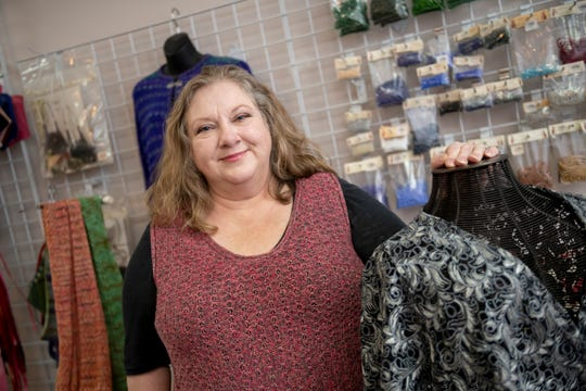 Amy Houghtalin, manager of City Knits in Harrison Twp., with her knitted items.