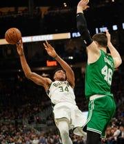 Milwaukee Bucks' Giannis Antetokounmpo passes in front of Boston Celtics' Aron Baynes.