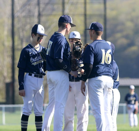 Elmira Notre Dame's Hunter Homerda, second from left, huddles with teammates during a 5-2 win over Watkins Glen/Odessa-Montour on May 8, 2019 at Watkins Glen High School.