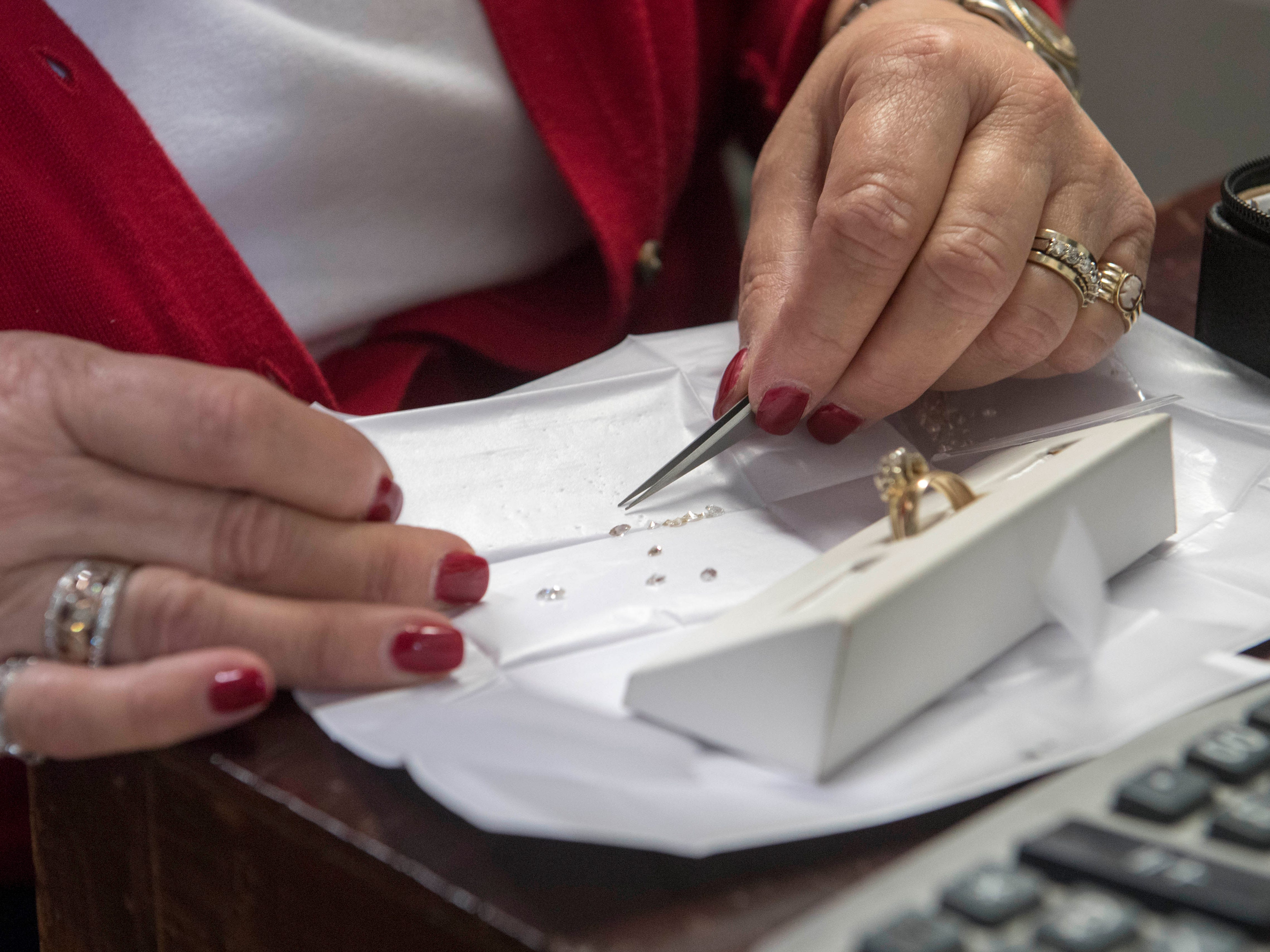 Owner Joan Turley picks out diamonds for a wedding ring Wednesday, April 10, 2019.  Turley Mfg. Jewelers is a third generation family own jewelry store in its 71st year in Downtown Evansville, Indiana.