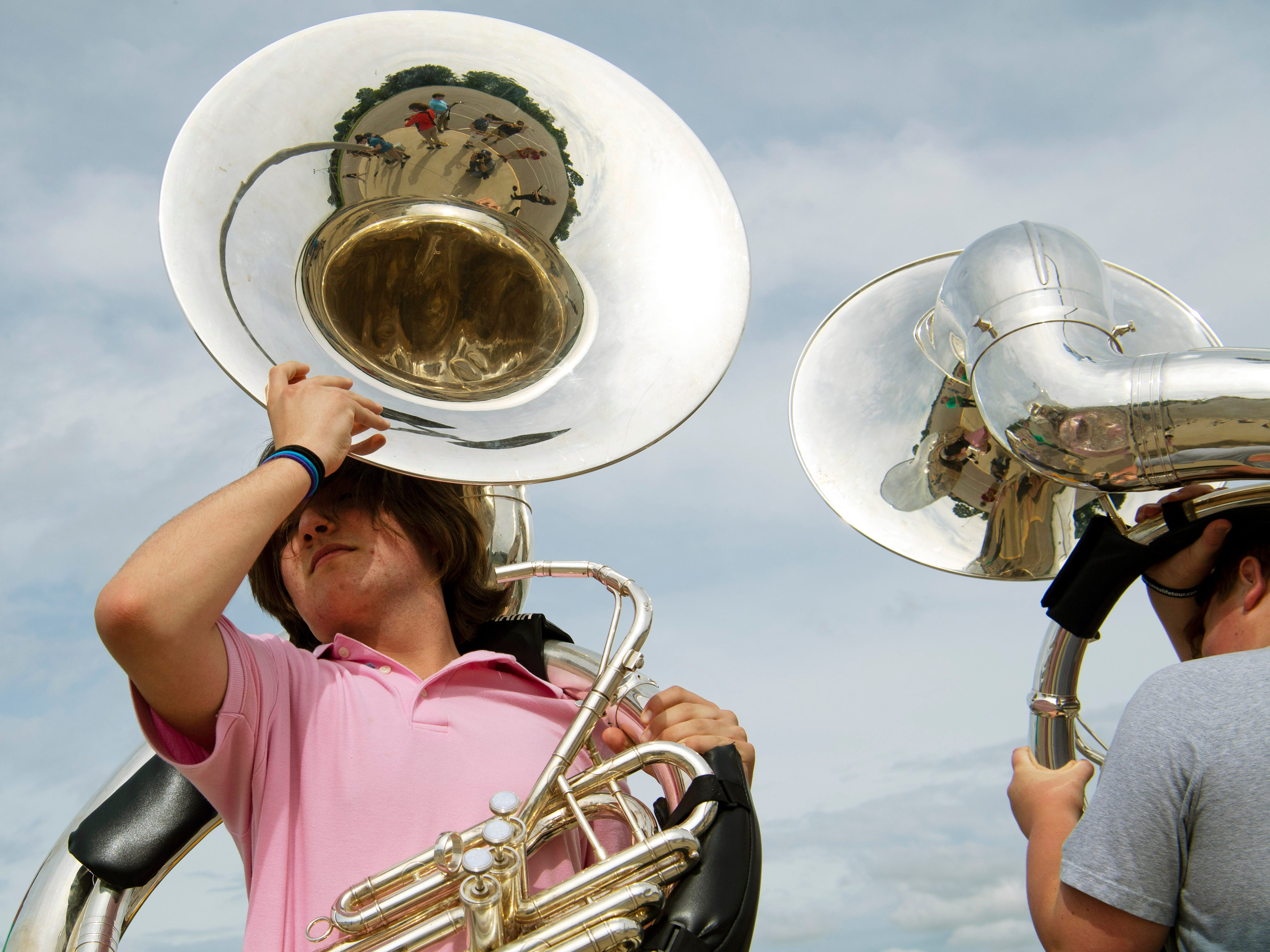 David Koehler, 14, a Thompkins Middle School 8th-grader, slips into a sousaphone during a Central Marching Band pre-camp Thursday evening.