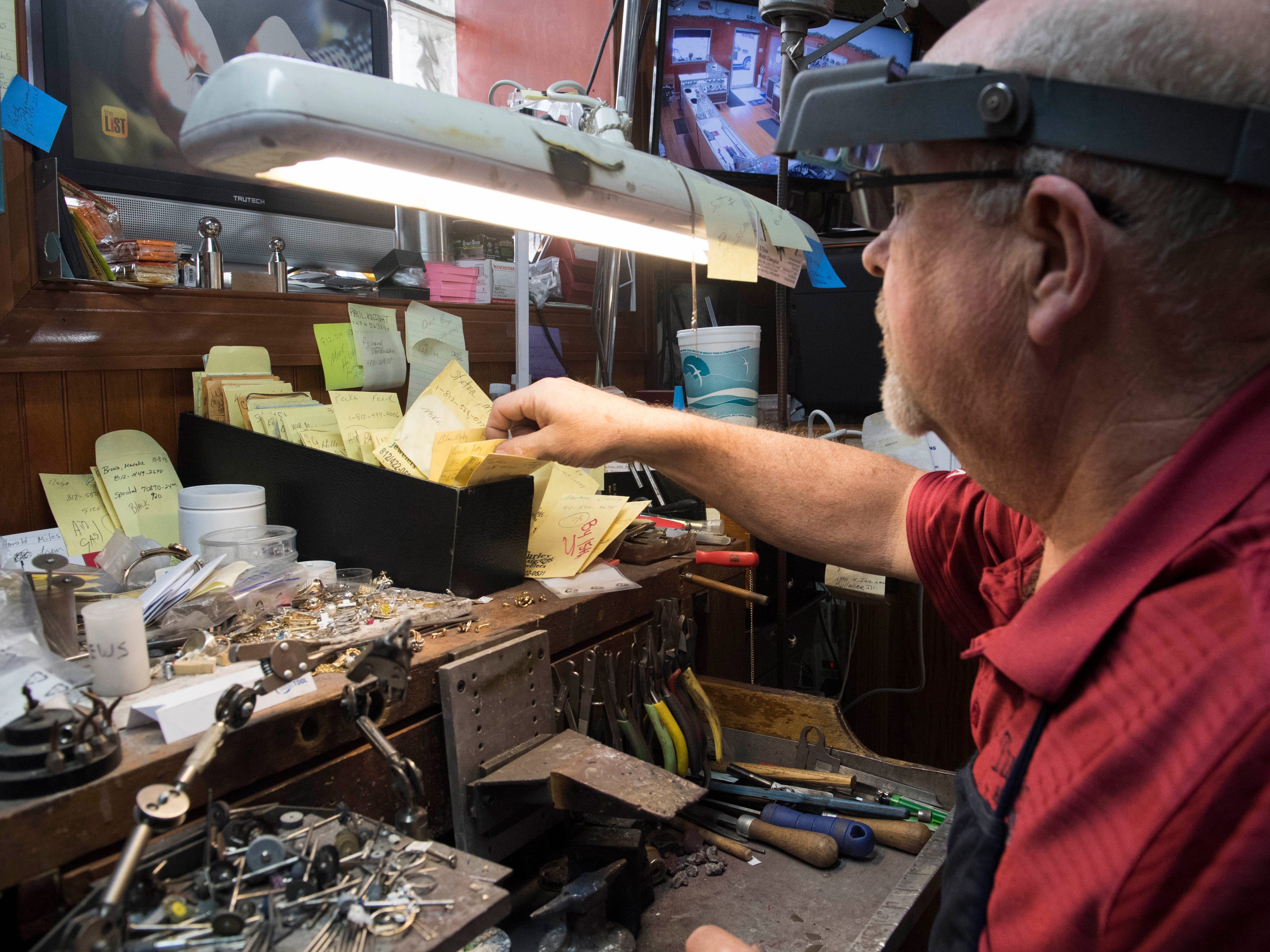 Owner Bryan Turley of Turley Mfg. Jewelers grabs a small envelope with jewelry to repair at his workbench Wednesday, April 10, 2019. Turley Mfg. Jewelers is a third generation family own jewelry store in its 71st year in Downtown Evansville, Indiana.