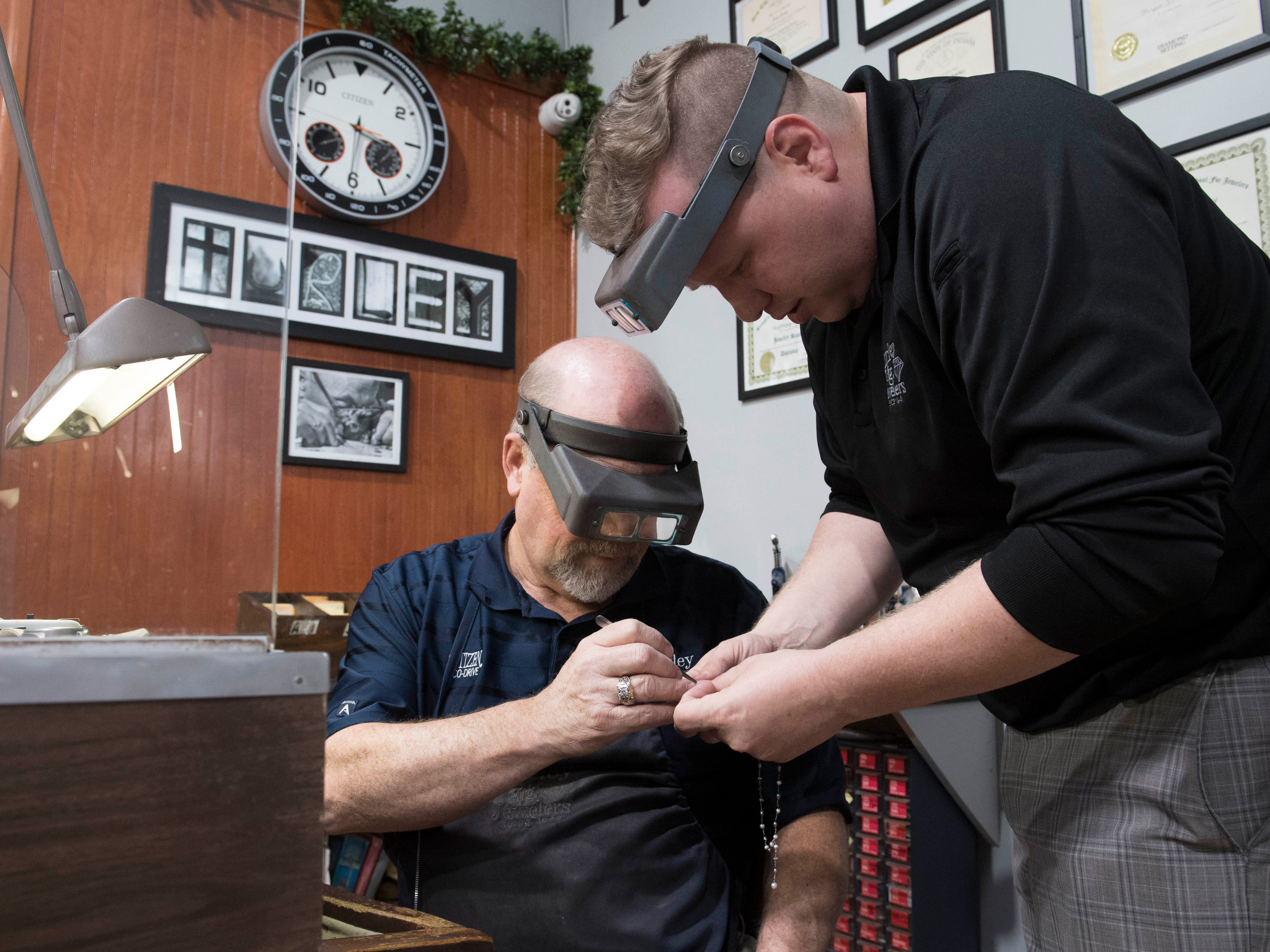 Bryan Turley, left, guides his son Matthew Turley, right, through a repair on a necklace Thursday, April 11, 2019.  Turley Mfg. Jewelers is a third generation family own jewelry store in its 71st year in Downtown Evansville, Indiana.