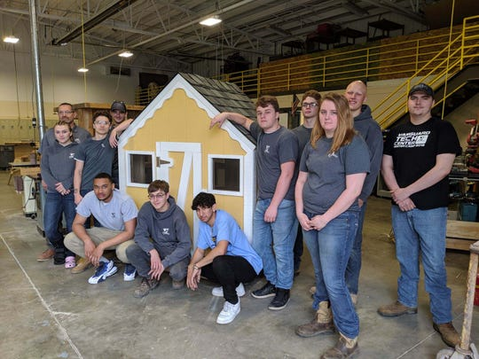Vanguard students in Dan Moscioni's building trades class stand next to a playhouse they built.