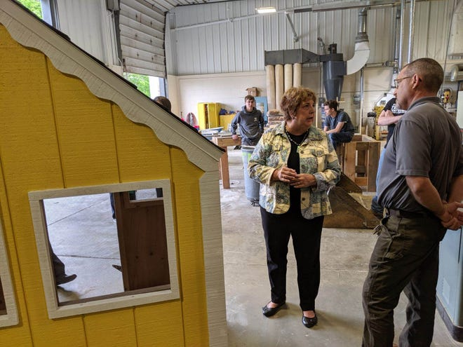 Habitat for Humanity Executive Director Donna Thatcher speaks with Vanguard Career Center teacher Dan Moscioni about a playhouse built by his building trades class.