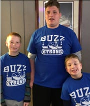 "Daniel Webster's sons, Noah, D.J. and Jonah wear ""Buzz Strong Tshirts."