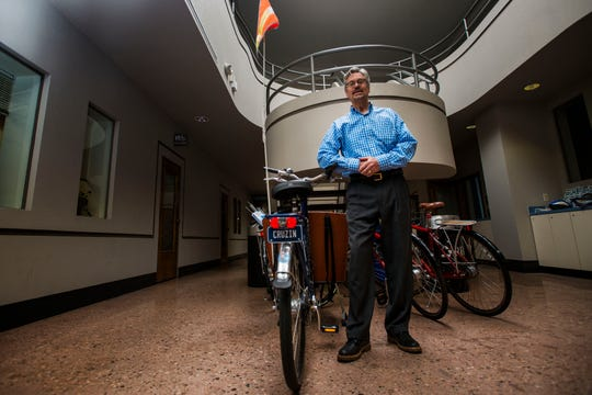 Senior planner with the city of Fort Collins Ted Shepard leans on one of the commons bikes available for employees to use while posing for a portrait at the Fort Collins Building Services office on Thursday, May 9, 2019, in Fort Collins, Colo.