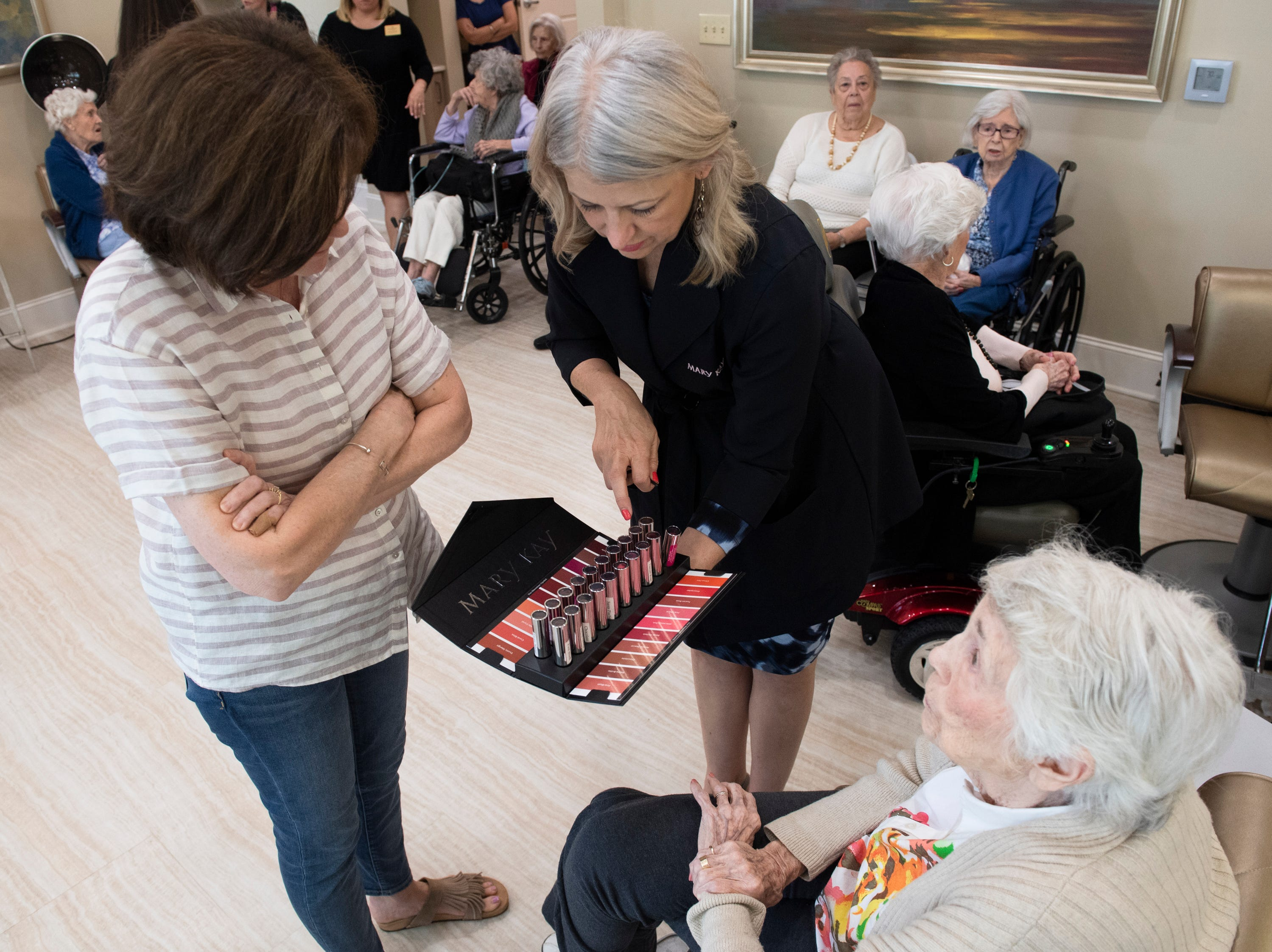 Sandra Johnston (center), from Mary Kay, helps Mary Jane Clayton and her mother, Dottie Sorensen, choose a lipstick color for Sorensen at Waterstone on Augusta Thursday, May 9, 2019. SYNERGY HomeCare of Greenville held a Mother's Day makeover party at the assisted living community.
