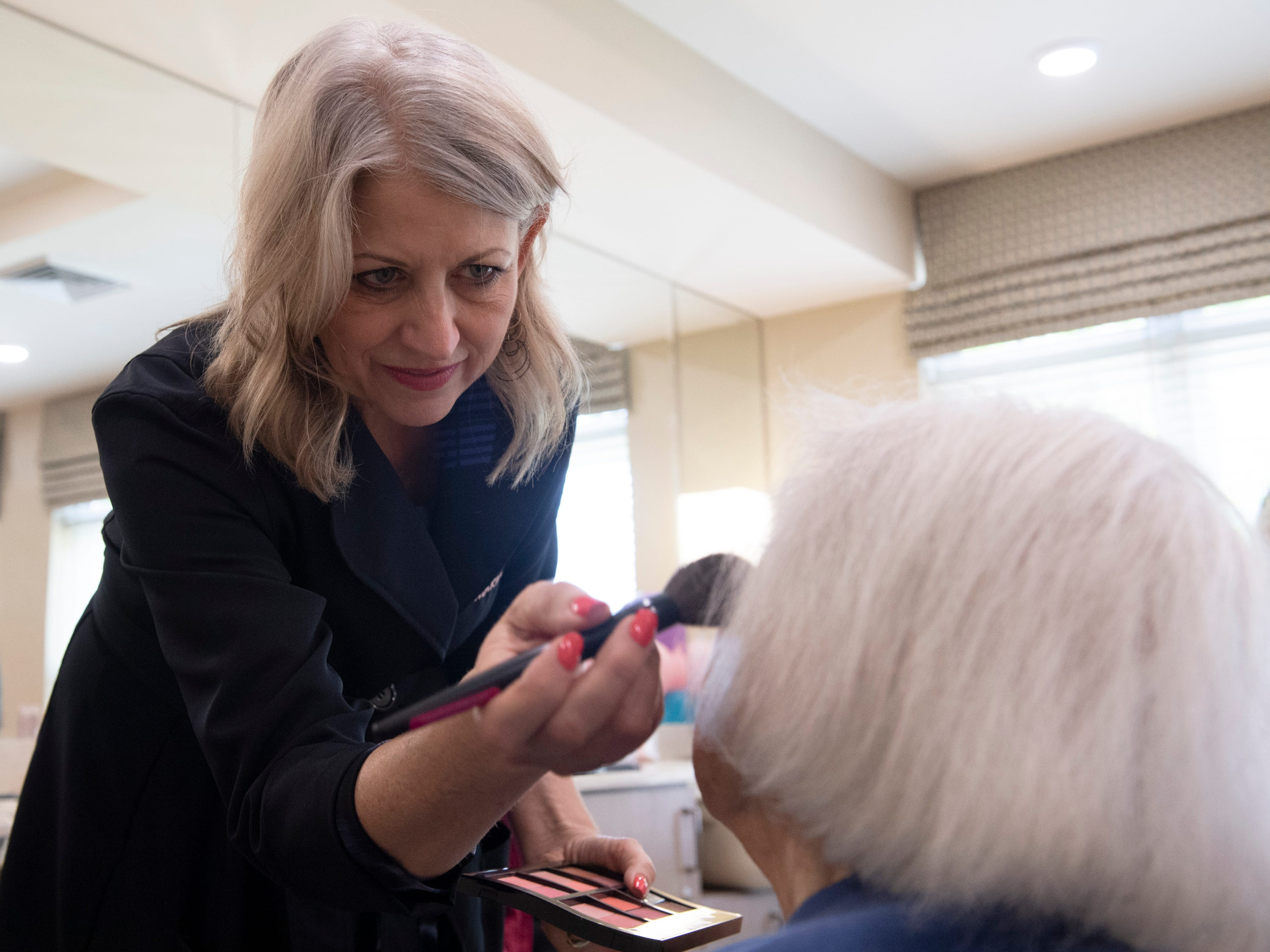 Sandra Johnston, from Mary Kay, applies make-up to Meador Kennedy at Waterstone on Augusta Thursday, May 9, 2019. SYNERGY HomeCare of Greenville held a MotherÕs Day makeover party at the assisted living community.