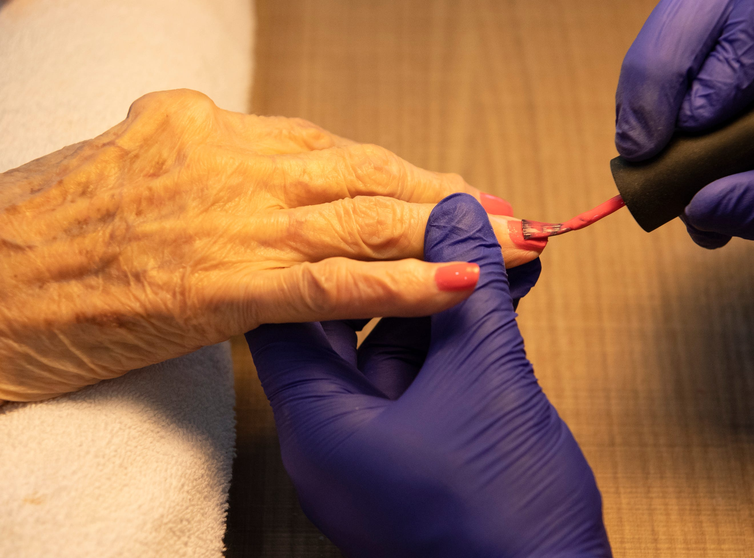 Santino Tedesco, director of community life at Waterston on Augusta, paints Meador Kennedy's nails Thursday, May 9, 2019. SYNERGY HomeCare of Greenville held a MotherÕs Day makeover party at the assisted living community.