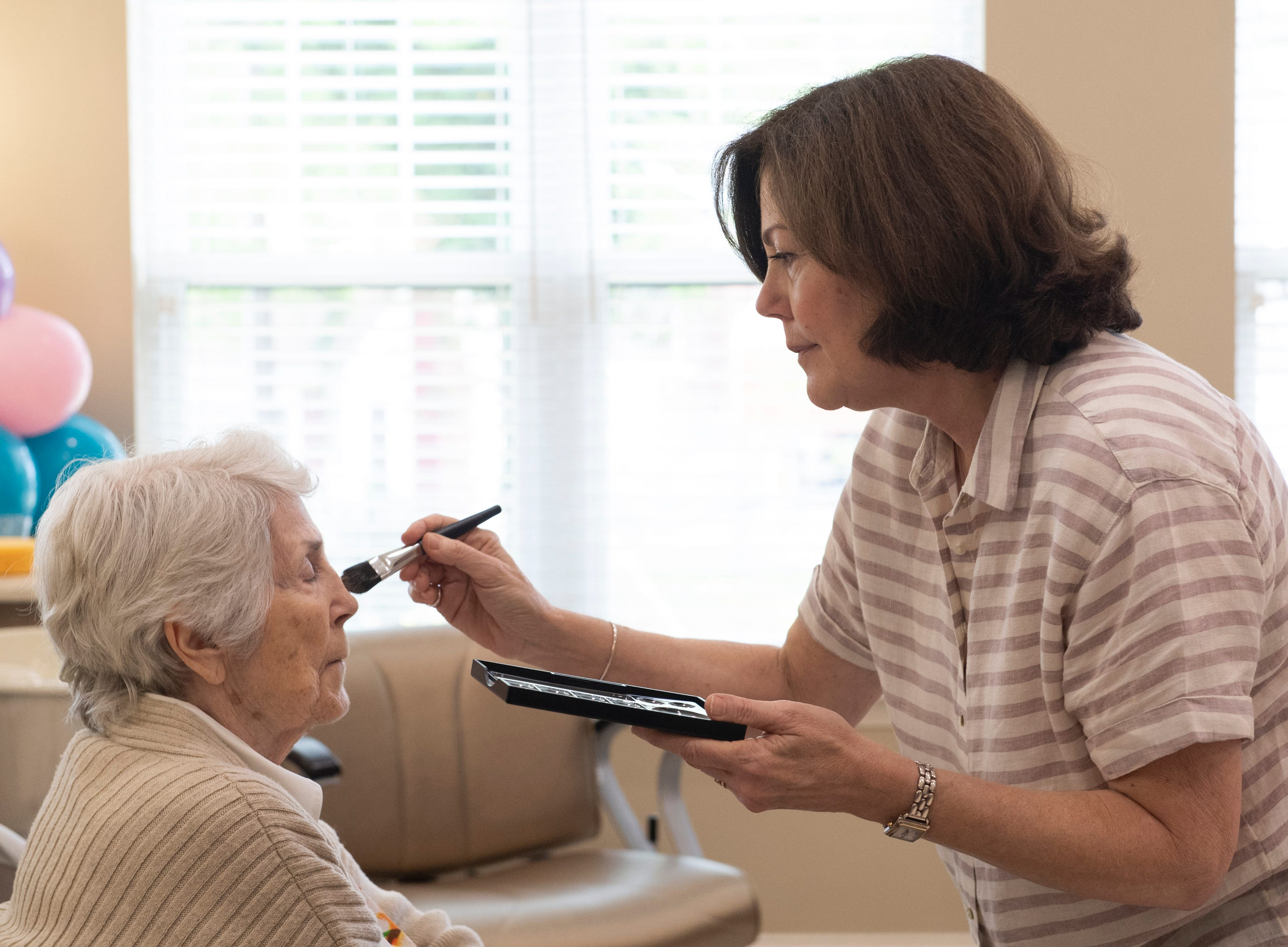 Mary Jane Clayton puts make-up on her mother, Dottie Sorensen at Waterstone on Augusta Thursday, May 9, 2019. SYNERGY HomeCare of Greenville held a MotherÕs Day makeover party at the assisted living community.