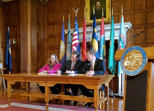 Democratic Rep. Mary Caferro, left, and Republican Rep. Ed Buttrey, right, look on as Democratic Gov. Steve Bullock signs a bill to continue Montana's Medicaid expansion program, Thursday, May 9, 2019 in Helena, Mont. Buttrey sponsored the bill that includes a work requirement, an improved asset test and increased premiums for people who remain on the program for more than a year. Caferro sponsored a Medicaid expansion bill that did not pass. The program provides health insurance to about 95,000 low-income residents. (AP Photo/Amy Beth Hanson)