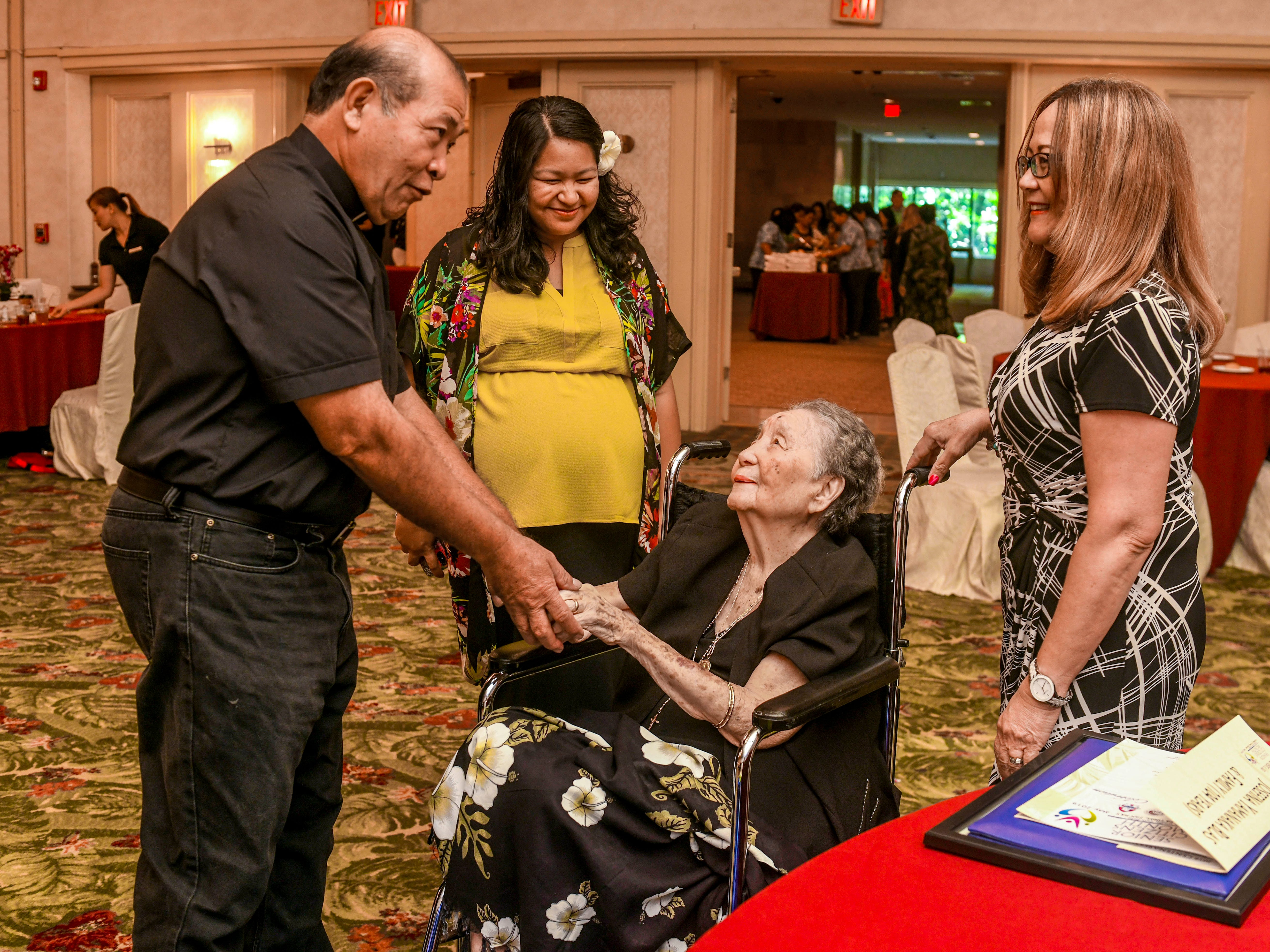 Santa Barbara Catholic Church's Deacon Romeo Hernandez, left, stops to chat with Josephina Dorotea Yamanaka Blas and other family members during the 2019 Centenarian Celebration, hosted by the Department of Public Health and Social Services, at the Pacific Star Resort & Spa in Tumon on Thursday, May 9, 2019. Blas, a mother of nine children, also surrounds herself with 42 grandchildren, 100 great-grandchildren, 28 great-great-grandchildren, according to her granddaughter Liza Mary Blas Matanane.