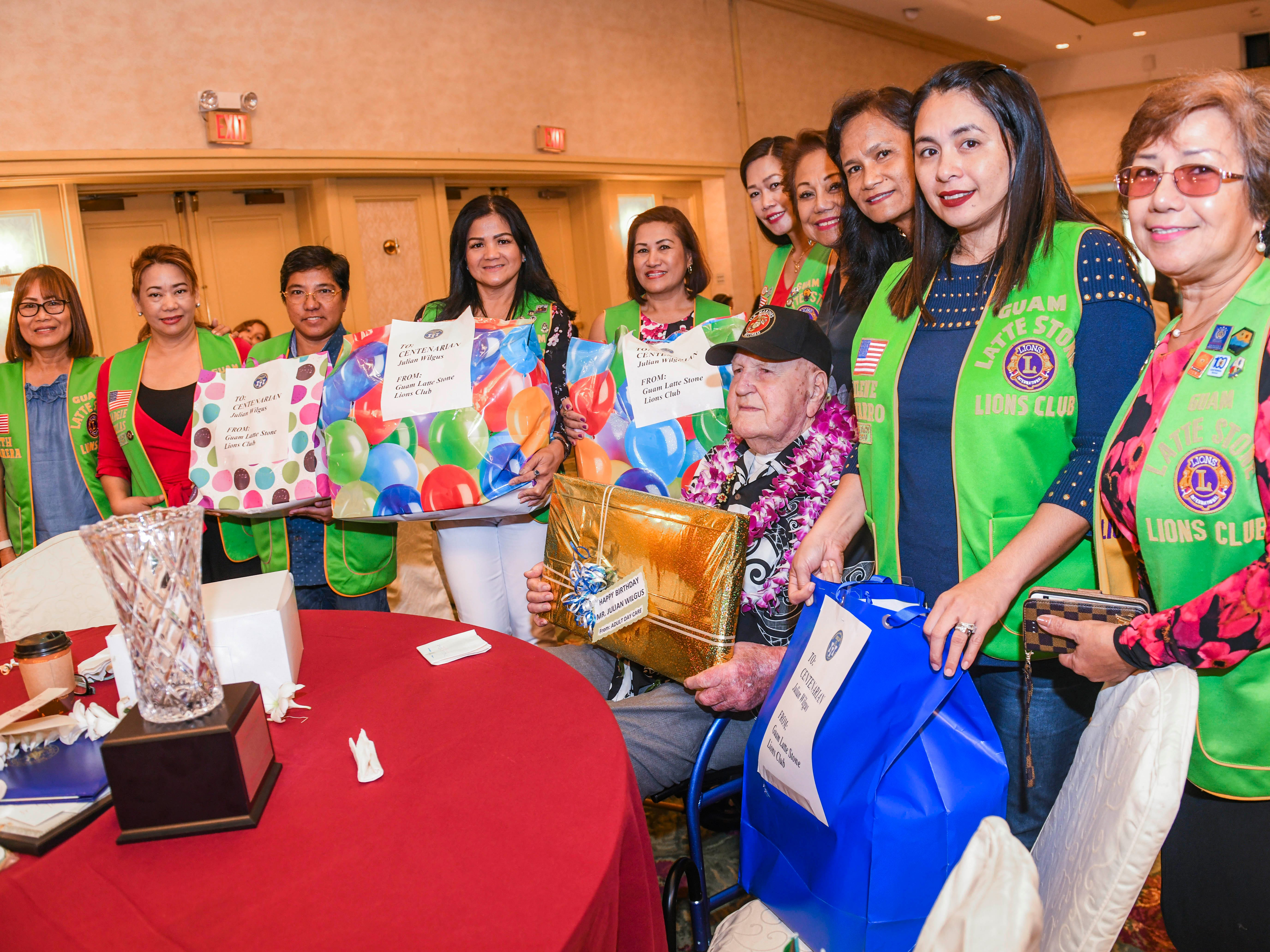 Julian Bryson Wilgus, 100, seated, receives gift from Guam Latte Stone Lion Club members during the 2019 Centenarian Celebration, hosted by the Department of Public Health and Social Services, held in conjunction with Senior Citizens Month, at the Pacific Star Resort & Spa in Tumon on Thursday, May 9, 2019.