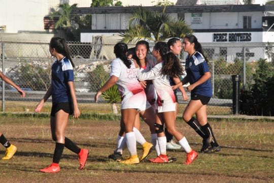 Knights Halle Wigsten, center, is congratulated by teammates after her header scored on a corner kick in the second half of St. John's 3-1 loss to the Academy Cougars in Tumon.