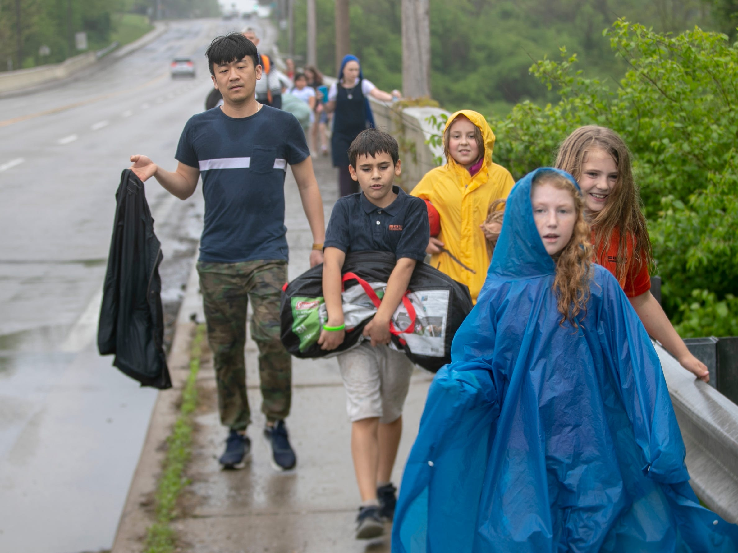 Students and teachers walk in a driving rain on Michigan Road during a workshop for fourth graders at International School of Indiana, Indianapolis, Thursday, May 1, 2019. They are walking about two miles from the lower grades campus to the middle school on Michigan Road.