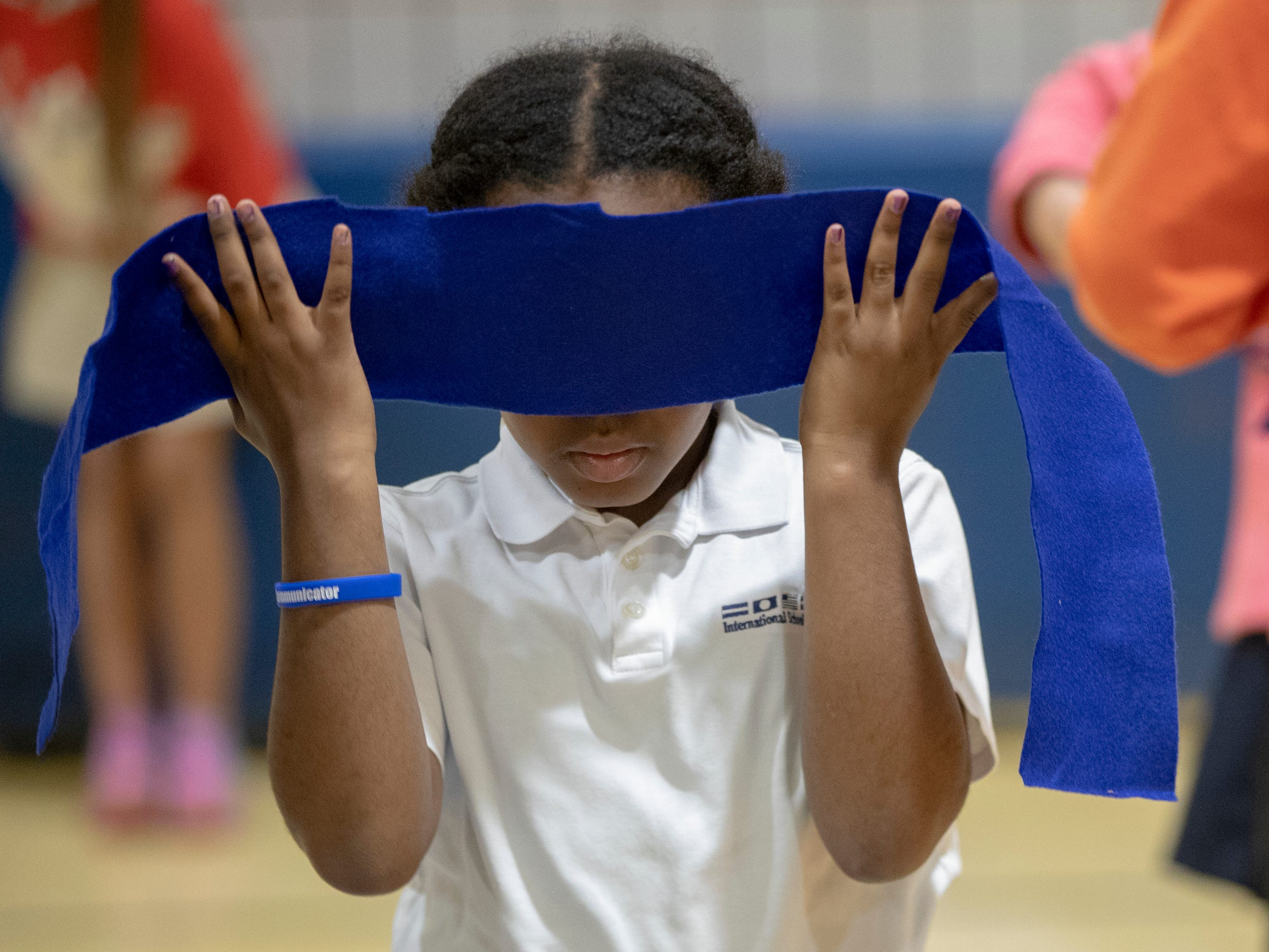 Alyssa Weems, 9, wraps a blindfold on her head during a workshop for fourth graders at International School of Indiana, Indianapolis, Thursday, May 1, 2019. In this exercise, she and other students are tasked with finding their 'family' in a darkened environment with only their voices and outstretched arms.