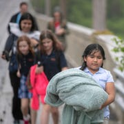 Teresa Avila-Guevara, 9, leads a group of students and teachers in a driving rain on Michigan Road during a workshop for fourth graders at International School of Indiana, Indianapolis, Thursday, May 1, 2019. They are walking about two miles from the lower-grades campus to their location on Michigan Road.