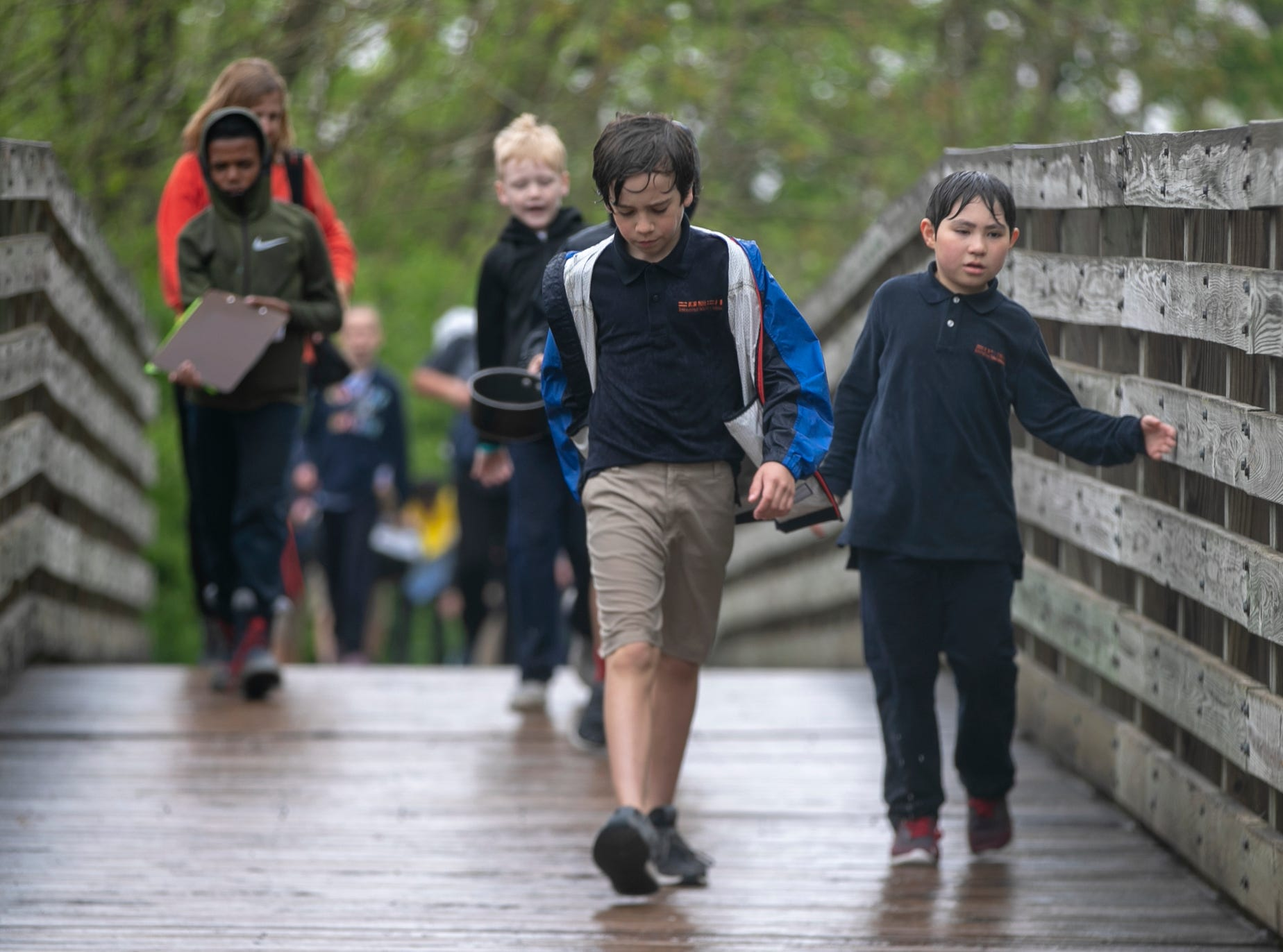 Students and teachers walk in a driving rain on the Central Canal Towpath during a workshop for fourth graders at International School of Indiana, Indianapolis, Thursday, May 1, 2019. The exercise, developed by the United Nations, is designed to simulate some of the hardships that refugees face when they're trying to leave their homeland.
