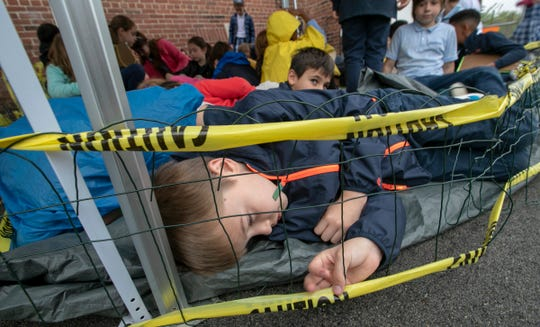 Henry Roberts lies down in a simulated holding facility during a workshop for fourth graders at International School of Indiana, Indianapolis, Thursday, May 1, 2019. The exercise, developed by the United Nations, is designed to simulate some of the hardships that refugees face when they're trying to leave their homeland.