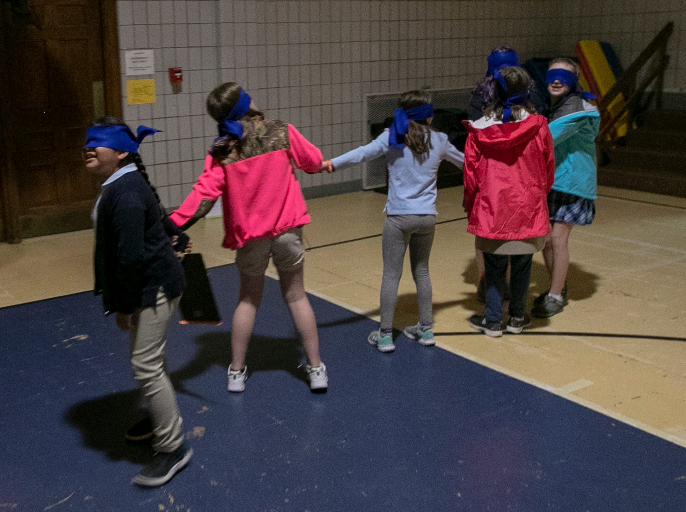 Blindfolded students call out for 'family' members during a workshop for fourth graders at International School of Indiana, Indianapolis, Thursday, May 1, 2019. The students had divided into families, separated in a darkened room with the sounds of a forest fire playing, and asked to find their simulated families again.