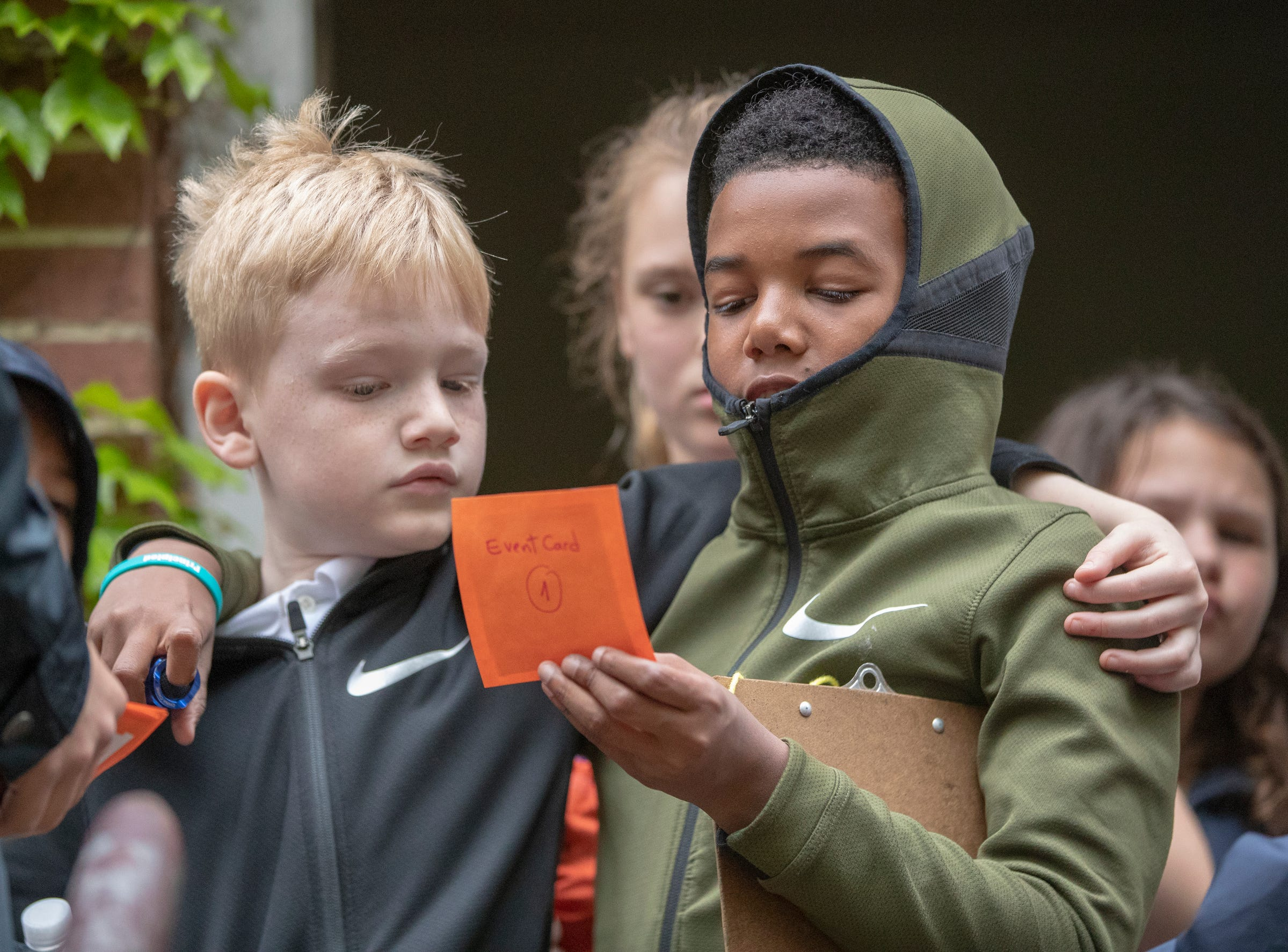 Oliver Driggers (left), and Dylan Rogers read a card during a workshop for fourth graders at International School of Indiana, Indianapolis, Thursday, May 1, 2019. The exercise, developed by the United Nations, is designed to simulate some of the hardships that refugees face when they're trying to leave their homeland.