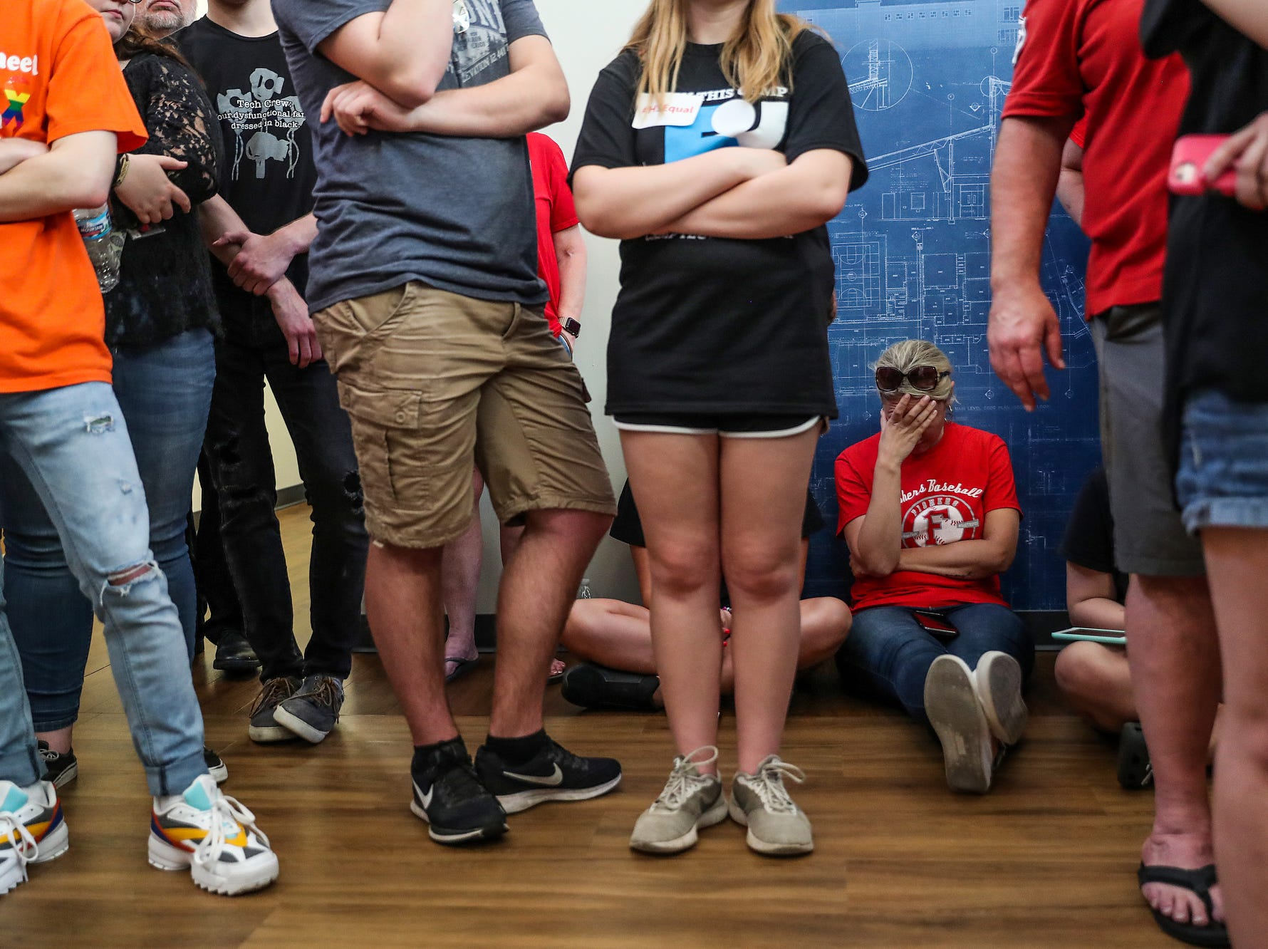 People sit and stand in the hallway to listen to the Hamilton Southeastern Schools board meeting at Cumberland Road Elementary in Fishers, Ind., Wednesday, May 8, 2019. The board voted 5-2 to adopt an anti-discrimination policy including language specifically prohibiting discrimination and harassment based on gender identity and sexual orientation.