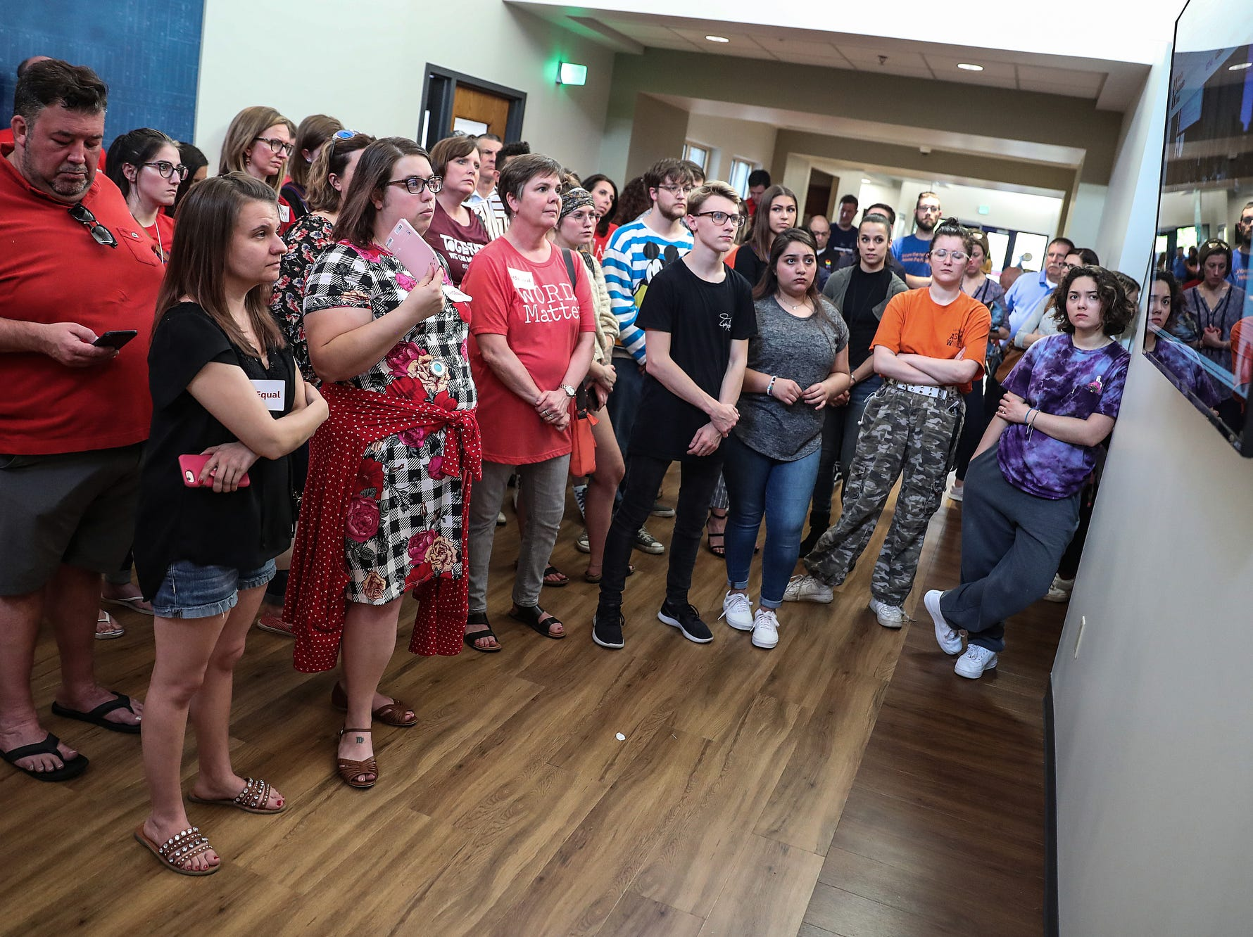 People watch a screen in the hallway outside the Hamilton Southeastern Schools board meeting at Cumberland Road Elementary in Fishers, Ind., Wednesday, May 8, 2019. The board voted 5-2 to adopt an anti-discrimination policy including language specifically prohibiting discrimination and harassment based on gender identity and sexual orientation.
