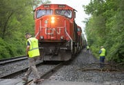 Workers at the scene of a fatal accident involving a pedestrian and a train at South Lynhurst Drive and Bertha Street in Indianapolis, on Thursday, May 9, 2019.