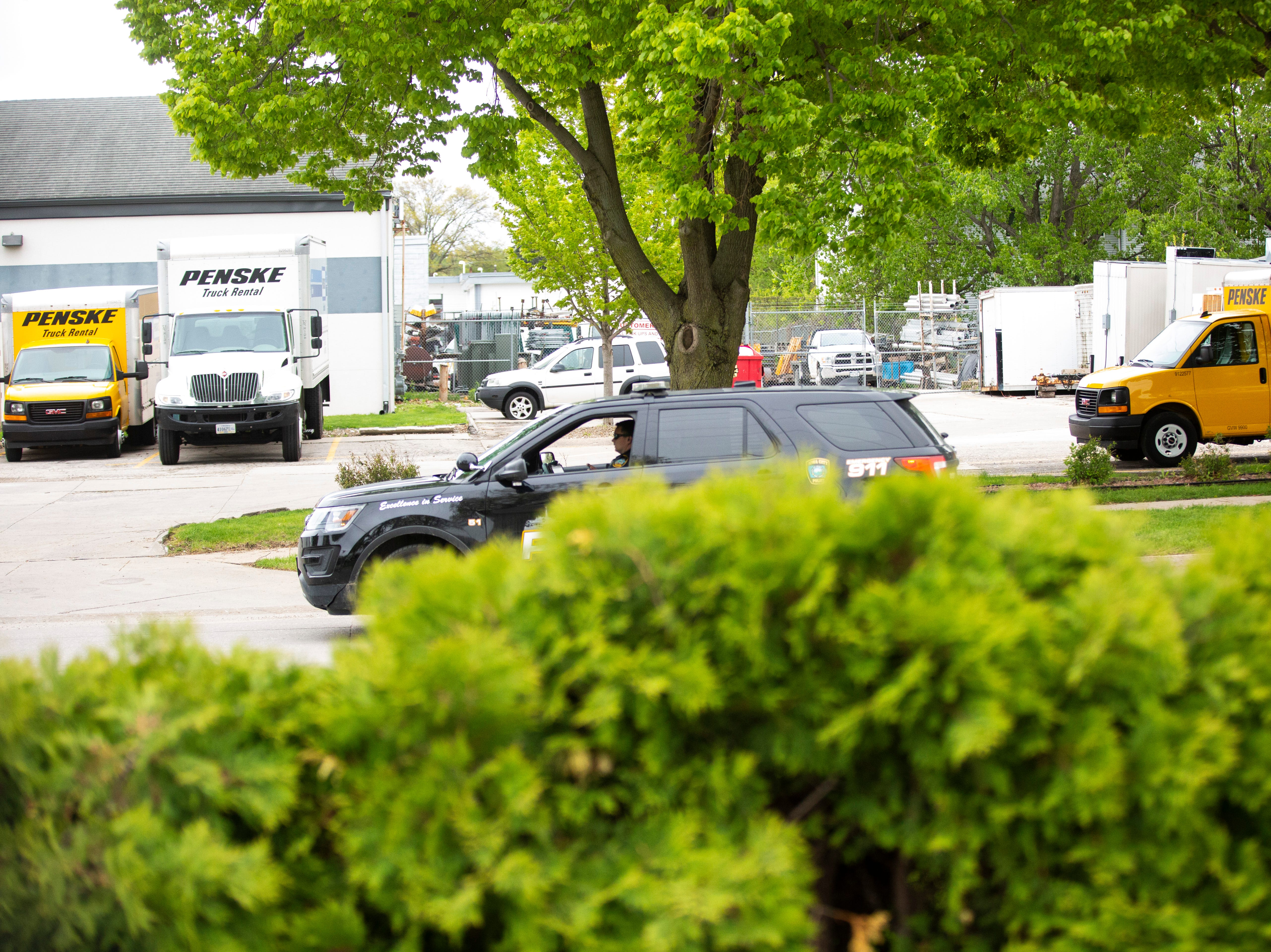 An Iowa City Police car drives past the parking lot where Penske vehicles are parked, Thursday, May 9, 2019, in front of Big Ten Rentals, south of Highway 6 in Iowa City, Iowa.