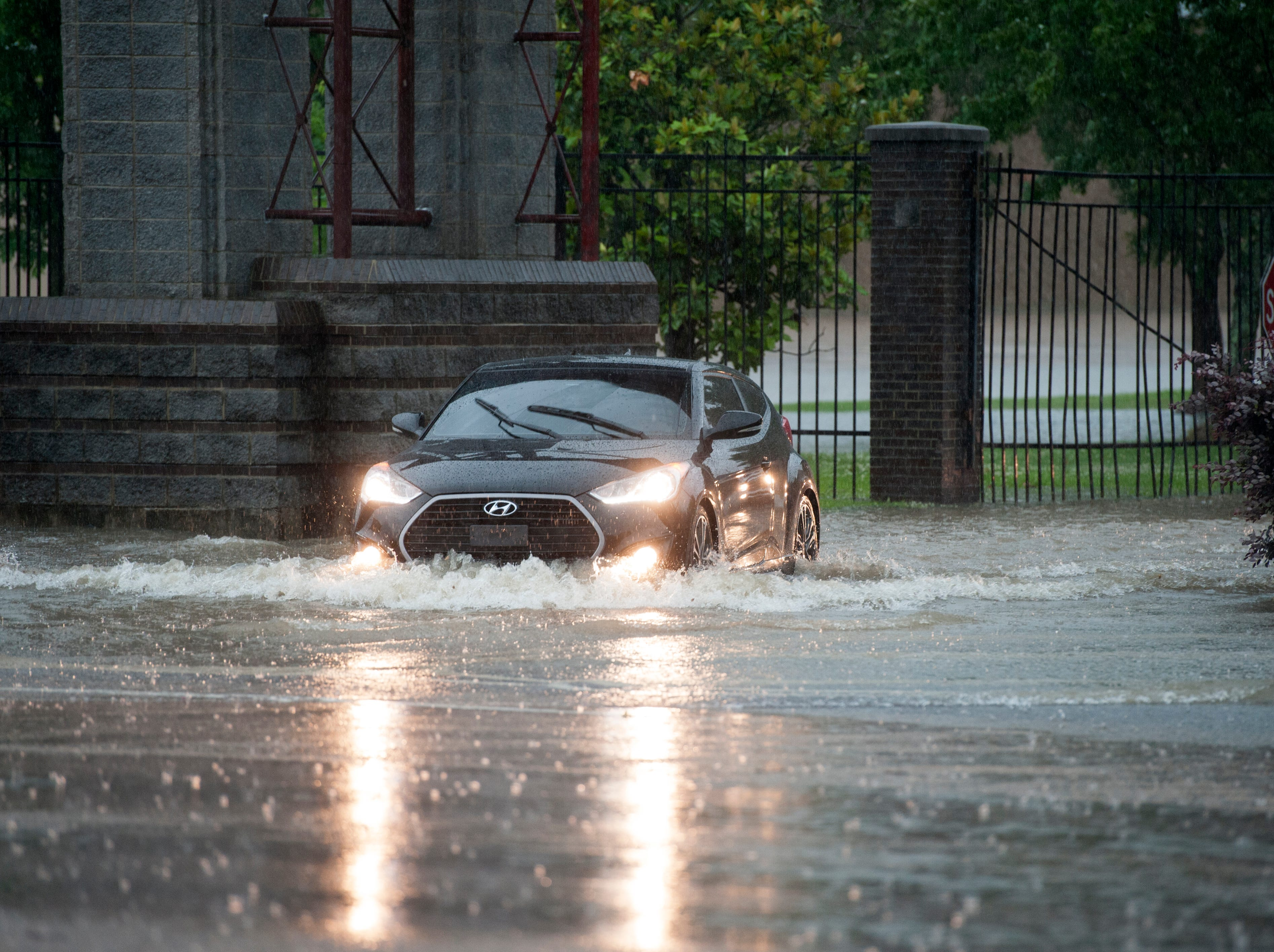 The driver of a Hyundai sedan goes through floodwaters at the High Street exit of the Mississippi State Fairgrounds Thursday. Thunderstorms are expected to continue throughout the morning with rain tapering off this evening. Thursday, May 9, 2019