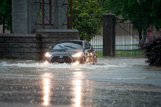 The driver of a Hyundai sedan goes through floodwaters on High Street Thursday in Jackson, Miss.