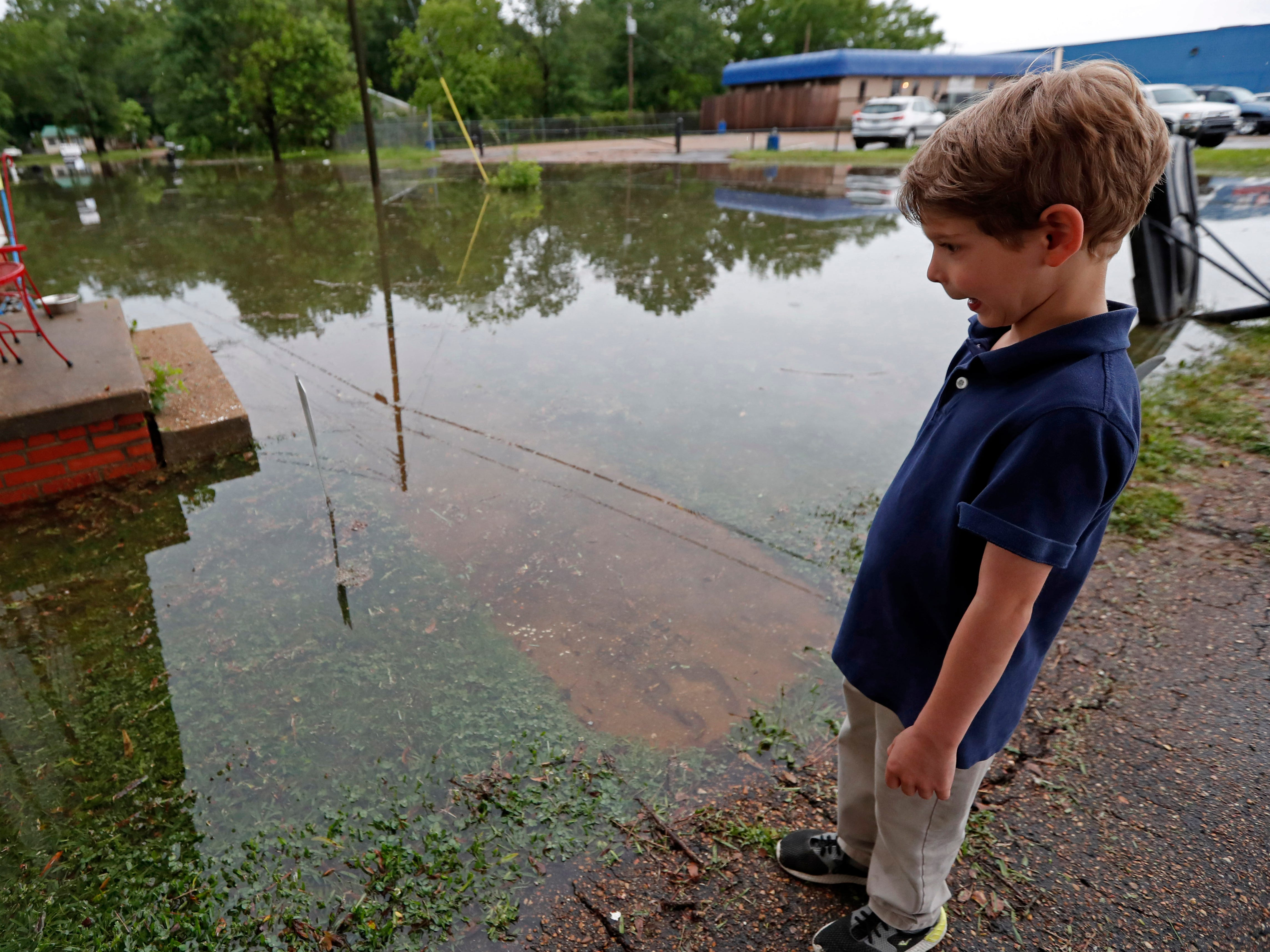 Trevor Clardy, 6, reacts to a worm swimming outside his Pearl, Miss., home, Thursday, May 9, 2019. Strong winds, tornado warnings and substantial rains added to the flash flooding throughout Mississippi.