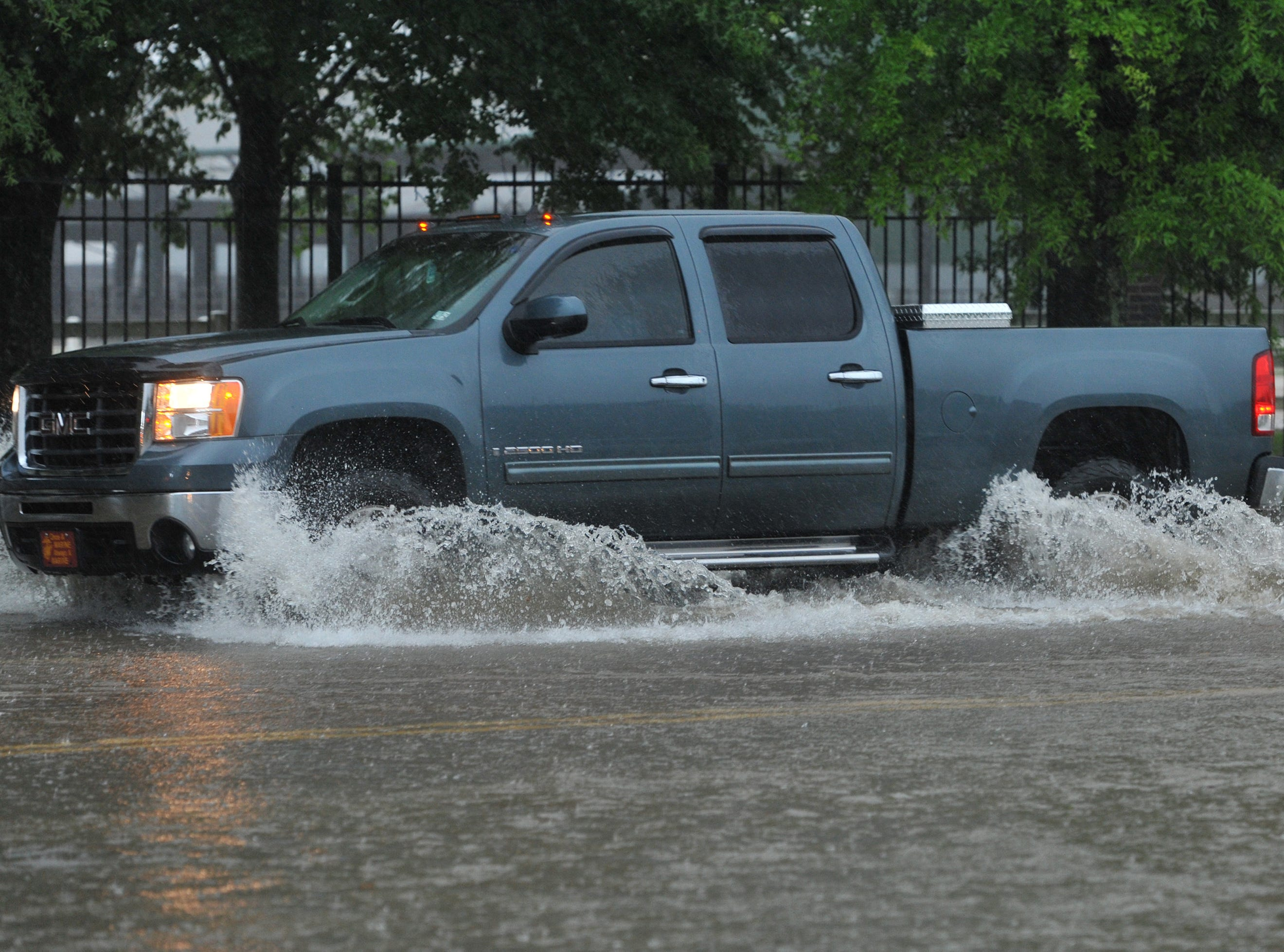 Water flies as a truck pushes through floodwaters on  High Street. Thursday, May 9, 2019