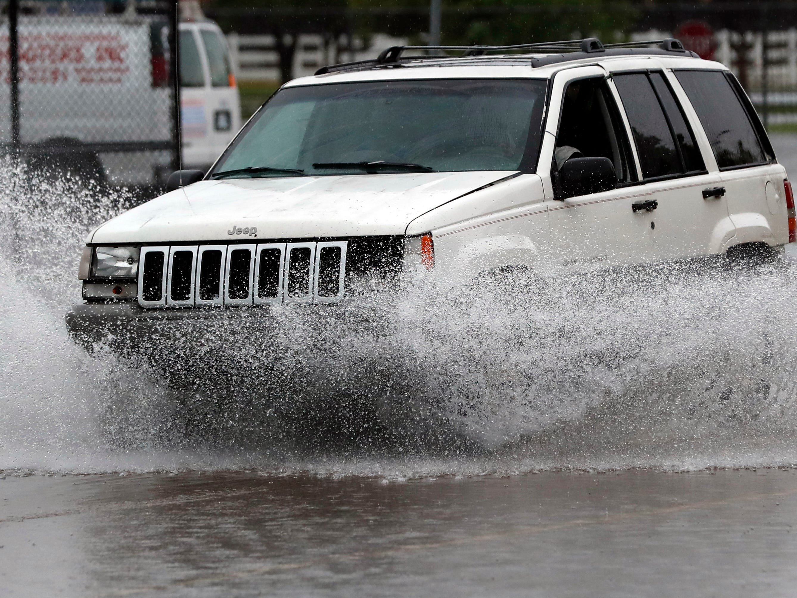 A vehicle drives through floodwaters near the state fairground in Jackson, Miss., Thursday, May 9, 2019, as strong winds, tornado warnings and substantial rains added to the flash flooding throughout Mississippi.