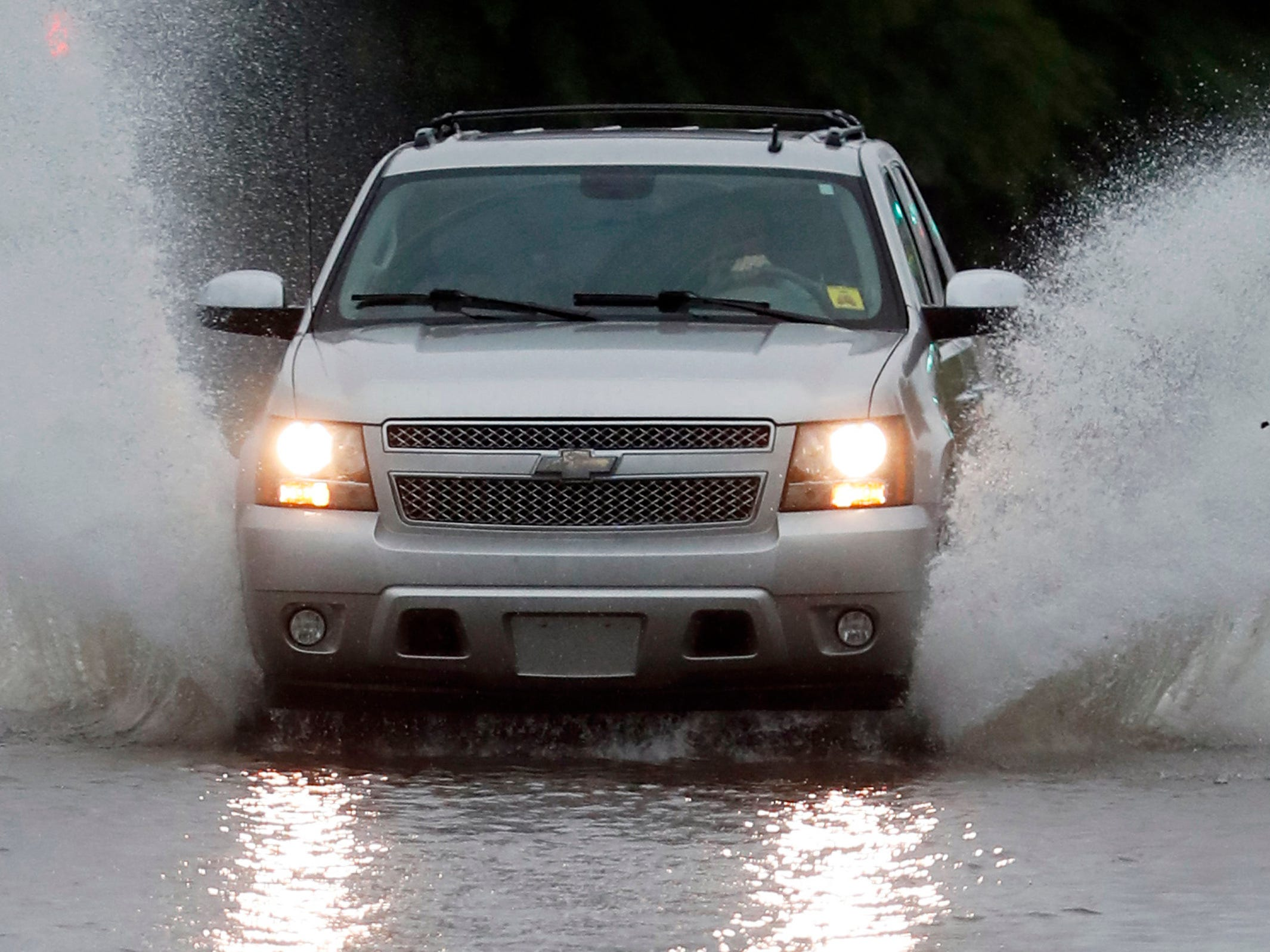 A vehicle drives through floodwaters in downtown Jackson, Miss., Thursday, May 9, 2019, as strong winds, tornado warnings and substantial rains added to the flash flooding throughout Mississippi.