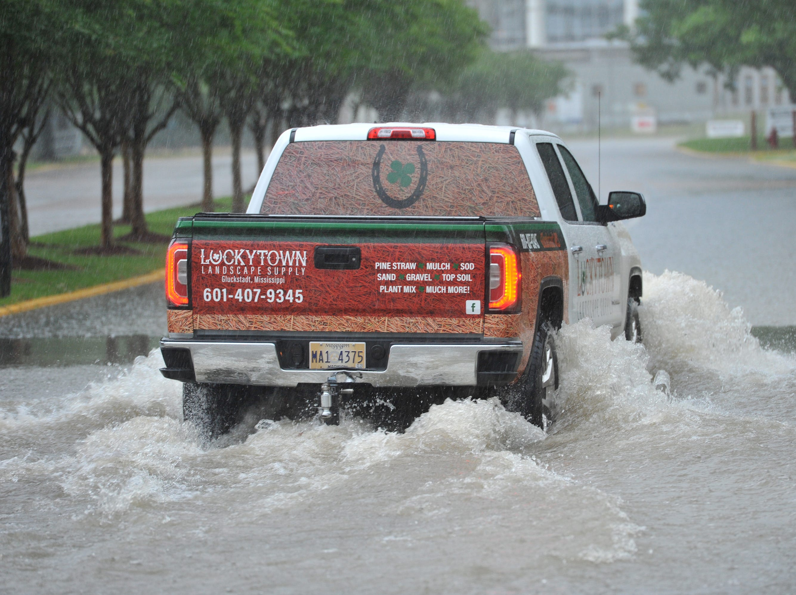 A pickup pushes though flood waters at the High Street entrance of the Mississippi State Faigrounds Thursday morning. Thursday, May 9, 2019