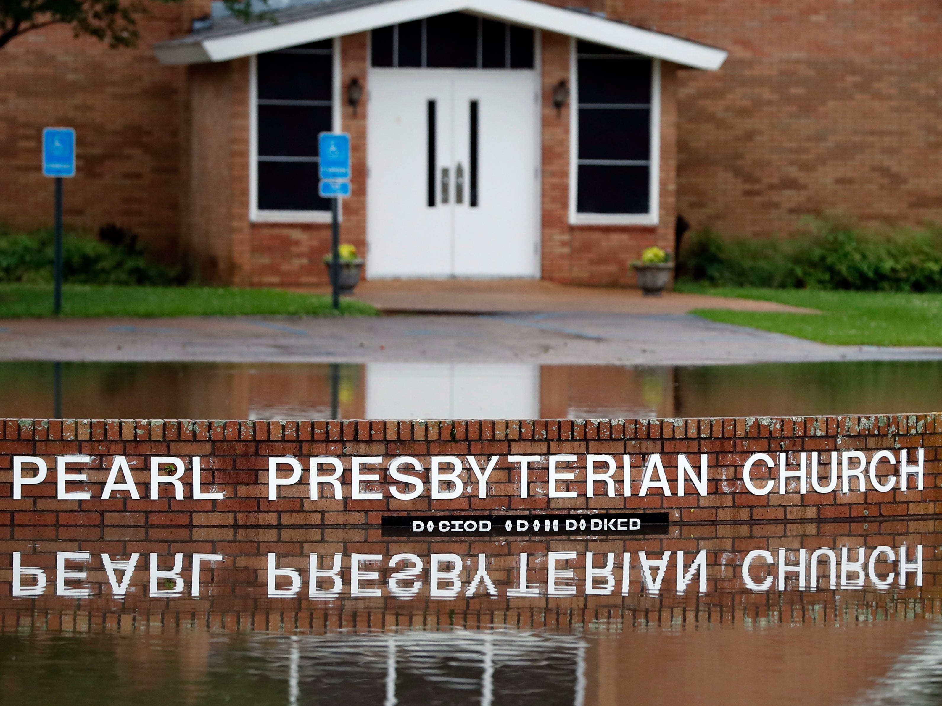 The Pearl Presbyterian Church's sign is reflected in floodwaters in Pearl, Miss., on Thursday, May 9, 2019. There is no pond on the property and the flash flooding filled up the parking lot as it surrounded the church.
