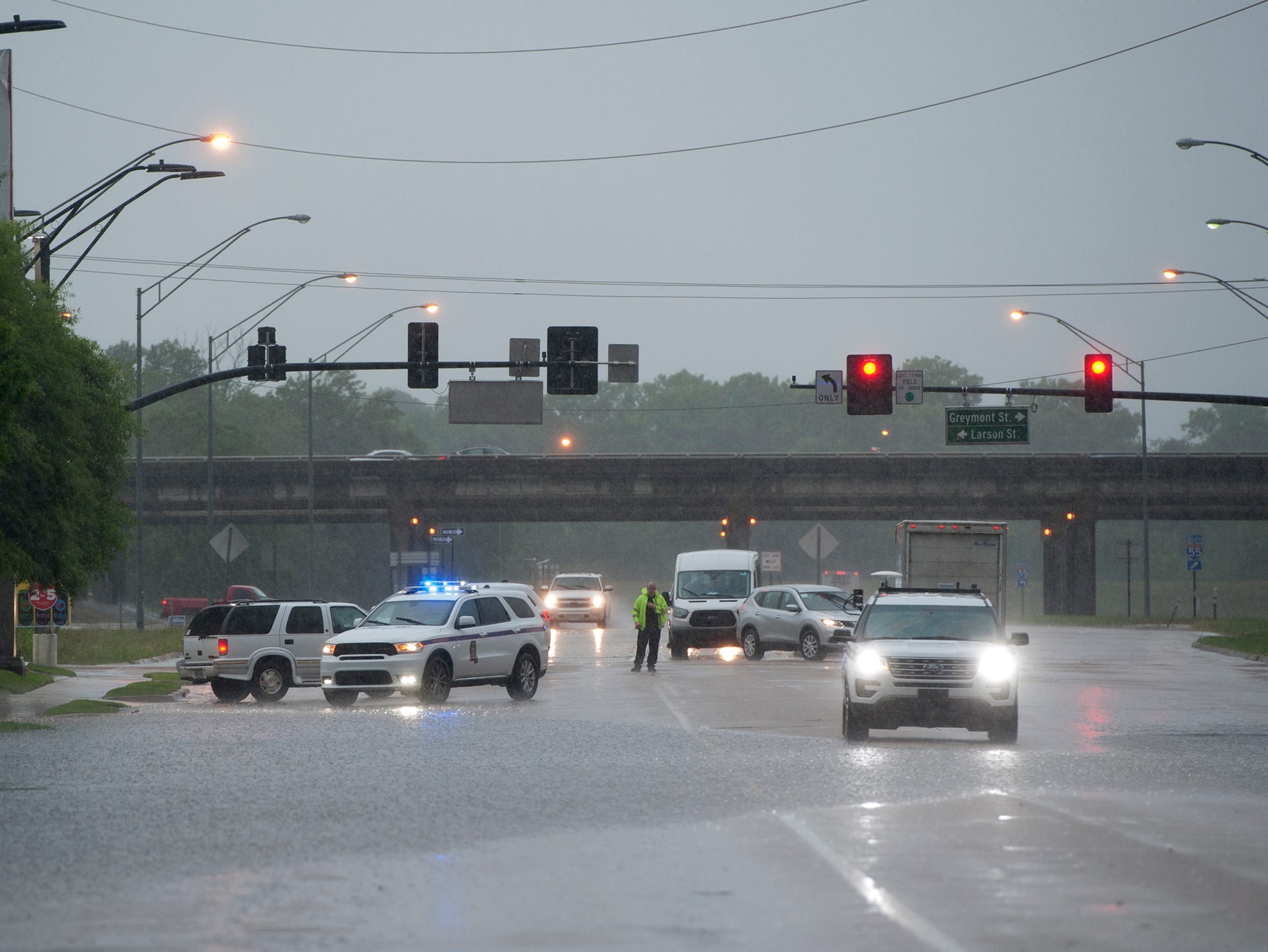 Jackson Police divert drivers from flooded areas on the east end of High Street Thursday morning. Thursday, May 9, 2019